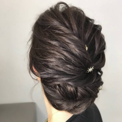 Textured dark hair updo with star clips in